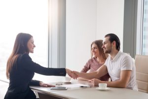 Happy young couple making real estate deal, handshake with agent