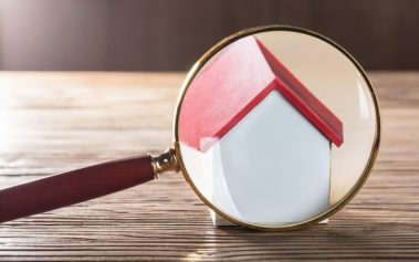 Close-up Of A House Model Seen Through Magnifying Glass On Wooden Table